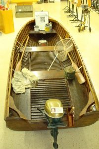 Wooden boat with outboard motor and paddles